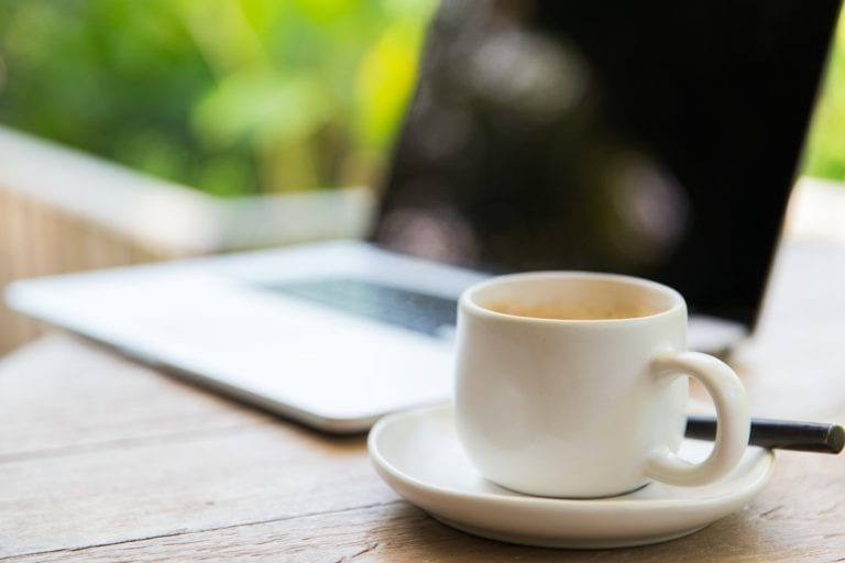 close up of coffee cup and laptop on table