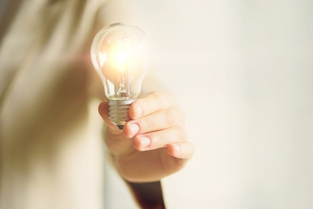 Woman hand holding light bulb on cream background with copy space. Creative idea, new business plan